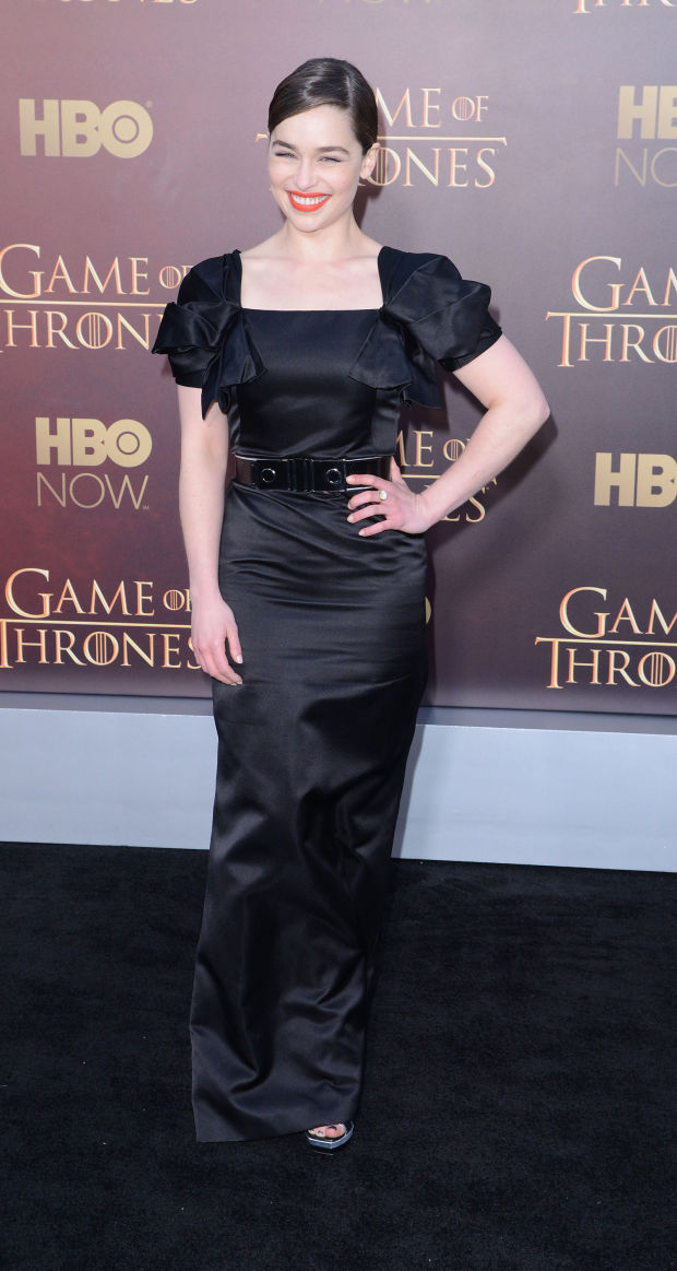 Emilia Clarke in a black satin gown.