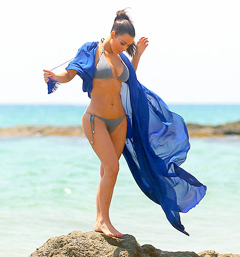 Kim Kardashian works a sexy bikini and long blue robe on the beach.