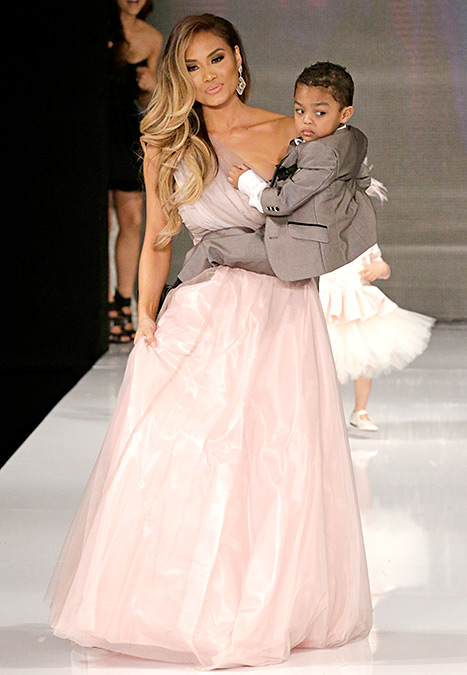 Daphne Joy carrying her son, Sire Jackson in the Isabella Couture runway show, one of the 3 children's brands runway show in Hollywood on March 10, 2015.