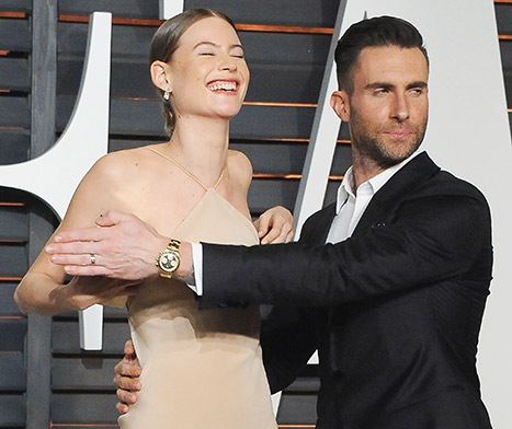 Adam Levine helps cover his wife Behati Prinsloo after she suffered a wardrobe malfunction at the 2015 Vanity Fair Oscar Party.