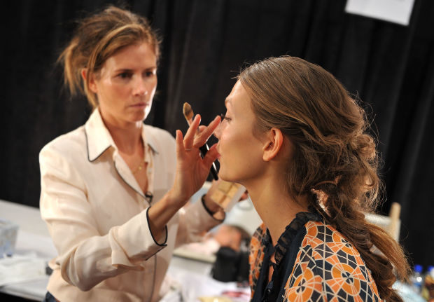 Gucci Westman applying makeup to Karlie Kloss at the J. Mendel spring 2012 show.