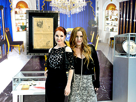Priscilla Presley and Lisa Marie pose in front of the Elvis memorabilia at the