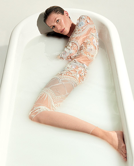 Gisele Bundchen wears a nude lace dress in a bathtub for the 40th anniversary issue of Vogue Brazil.