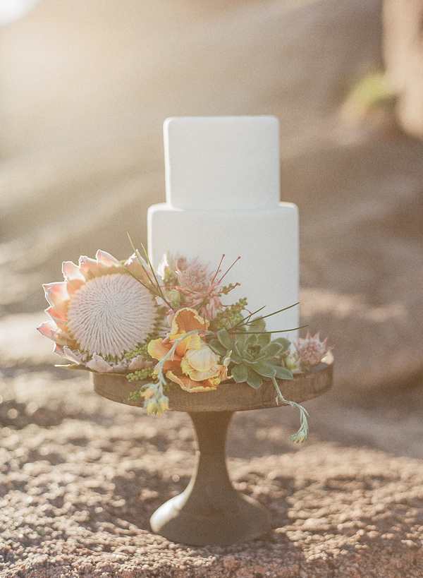 cake with protea decor - photo by Bella Reese Photography http://ruffledblog.com/graceful-desert-wedding-at-enchanted-rock