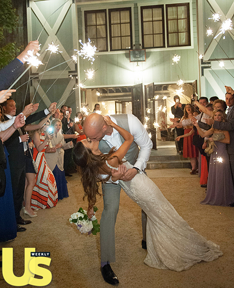 Jana Kramer and Michael Caussin kiss as their wedding guests hold sparklers