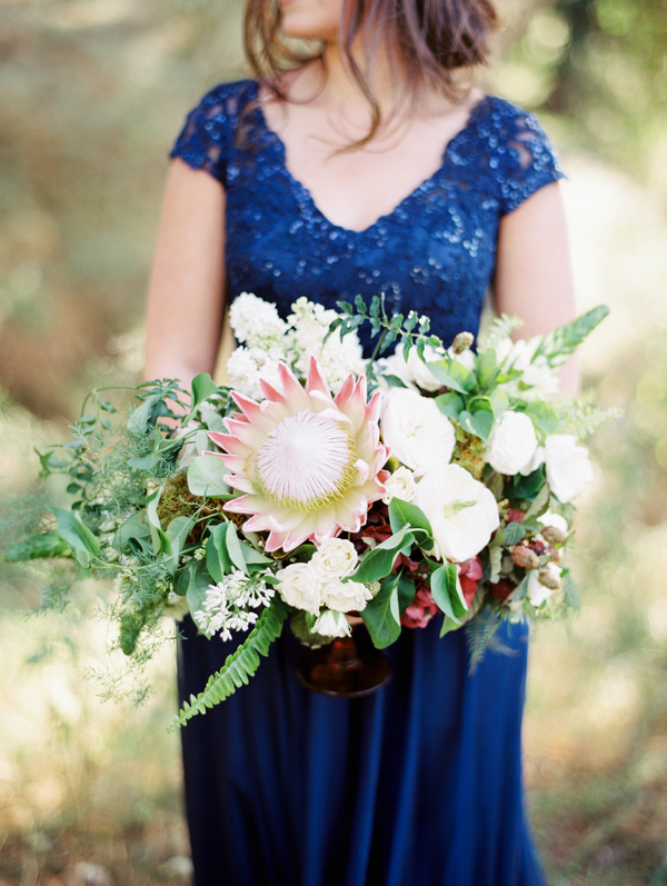 floral arrangement with protea - photo by Sposto Photography http://ruffledblog.com/countryside-wedding-with-cobalt-blue-and-crimson