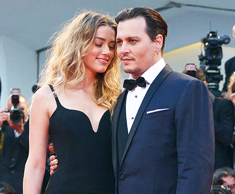 Amber Heard cuddles up to husband Johnny Depp on the red carpet at the Black Mass premiere in Venice.