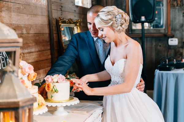 cake cutting - photo by Lora Grady Photography http://ruffledblog.com/fairytale-cottage-wedding-at-craven-farm