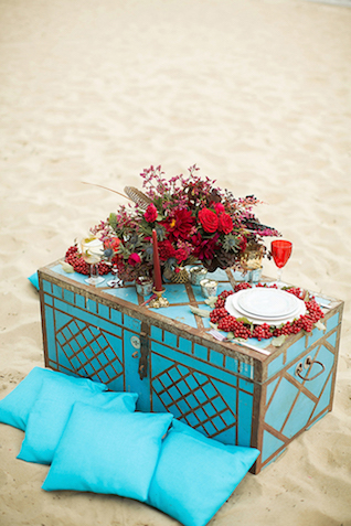 Turquoise trunk and pillows with red floral centerpiece | Sergey Bulychev and Sergey Ulanov | see more on: http://burnettsboards.com/2016/02/free-wind-beach-wedding-editorial/