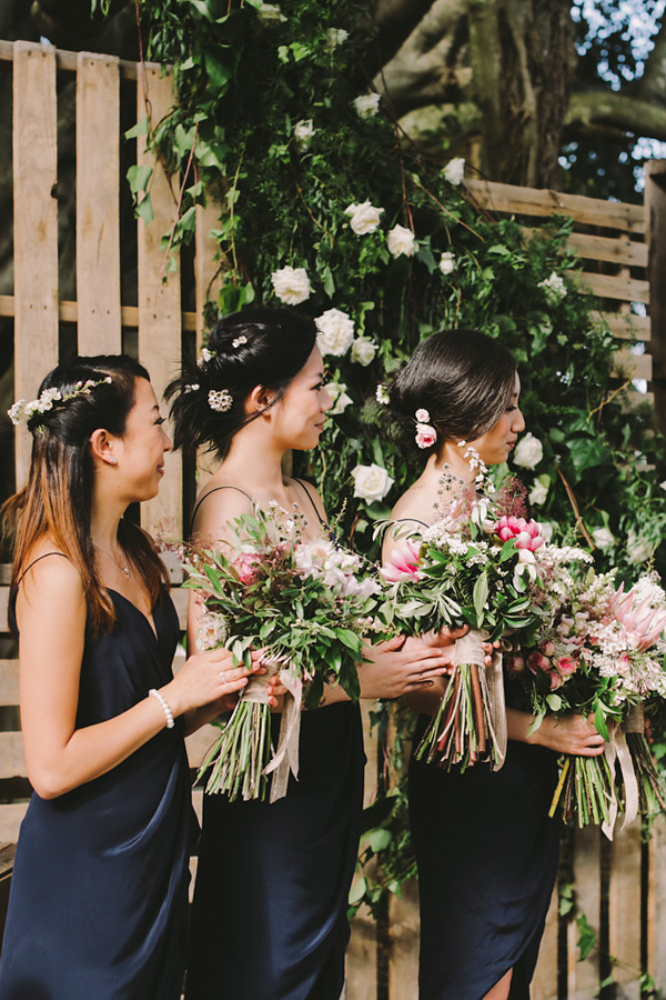 bridesmaids during ceremony - photo by Lara Hotz Photography http://ruffledblog.com/botanical-australian-barn-wedding