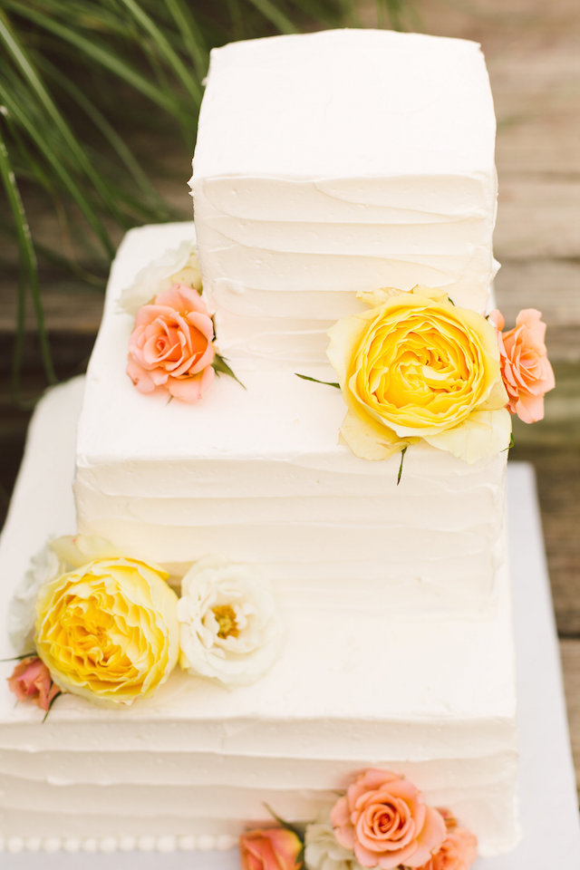 White wedding cake with peach and yellow flowers | Photography: Brooke Michelle Photography