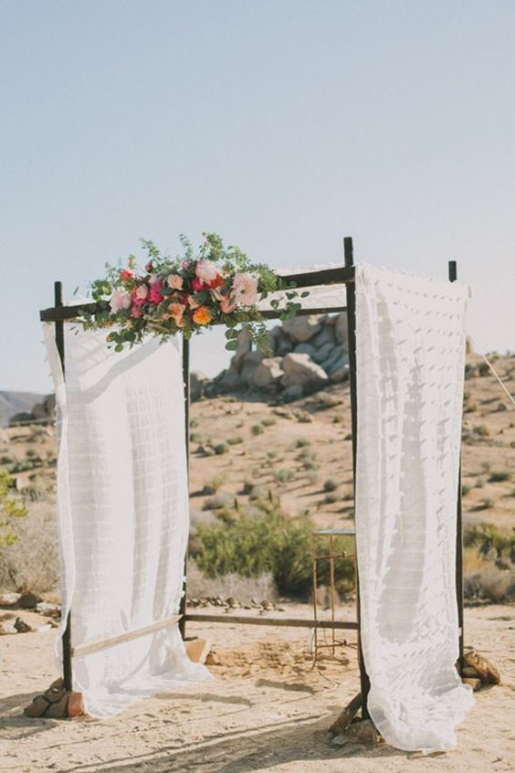 flowy arch decorated with flowers right in the desert