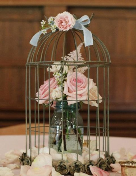 Table centerpiece with birdcage and vase with flowers