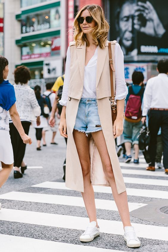 long beige vest, denim shorts and a white shirt