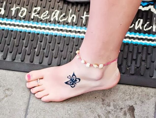small butterfly tattoo on a foot