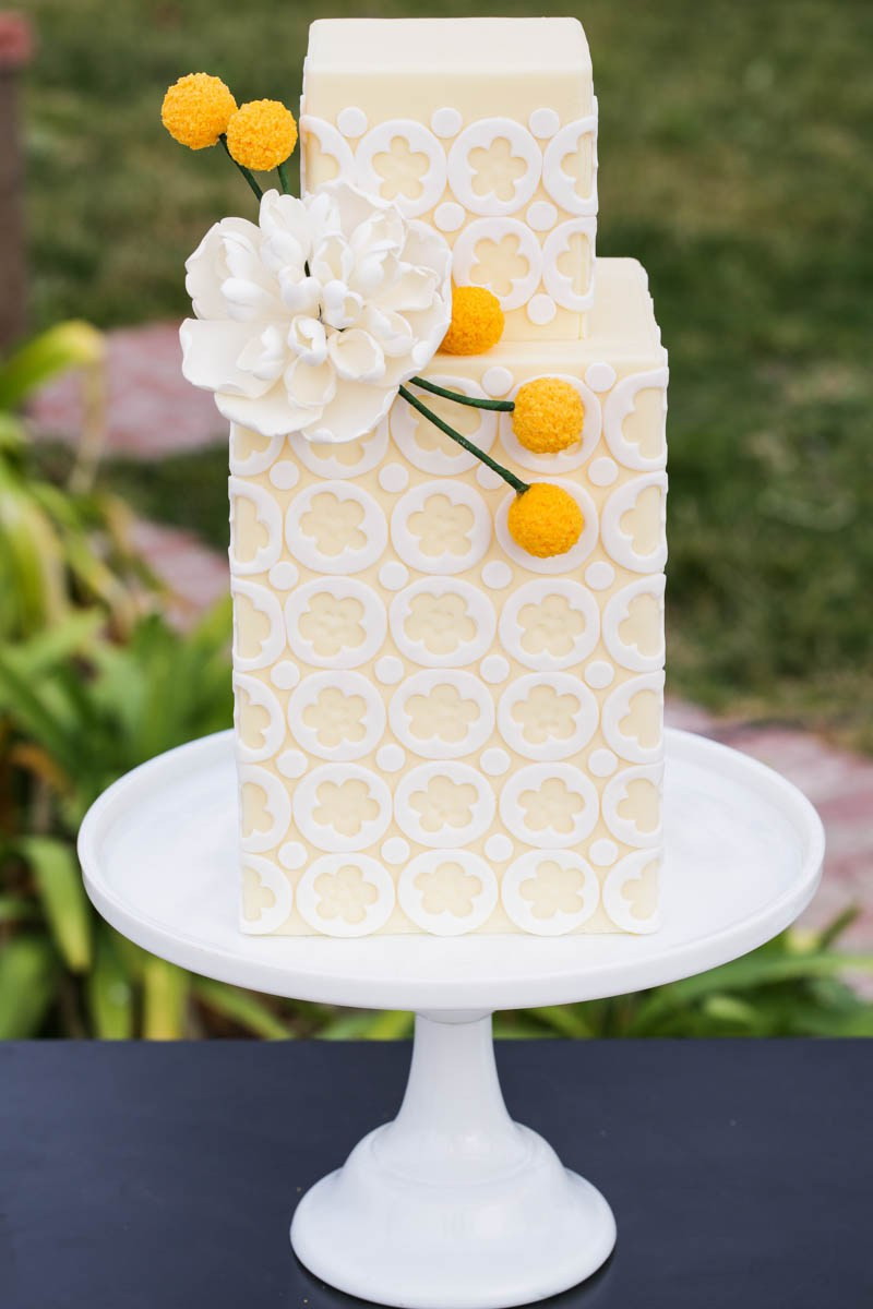 The cake was done in yellow and white and decorated with a flower and billy balls