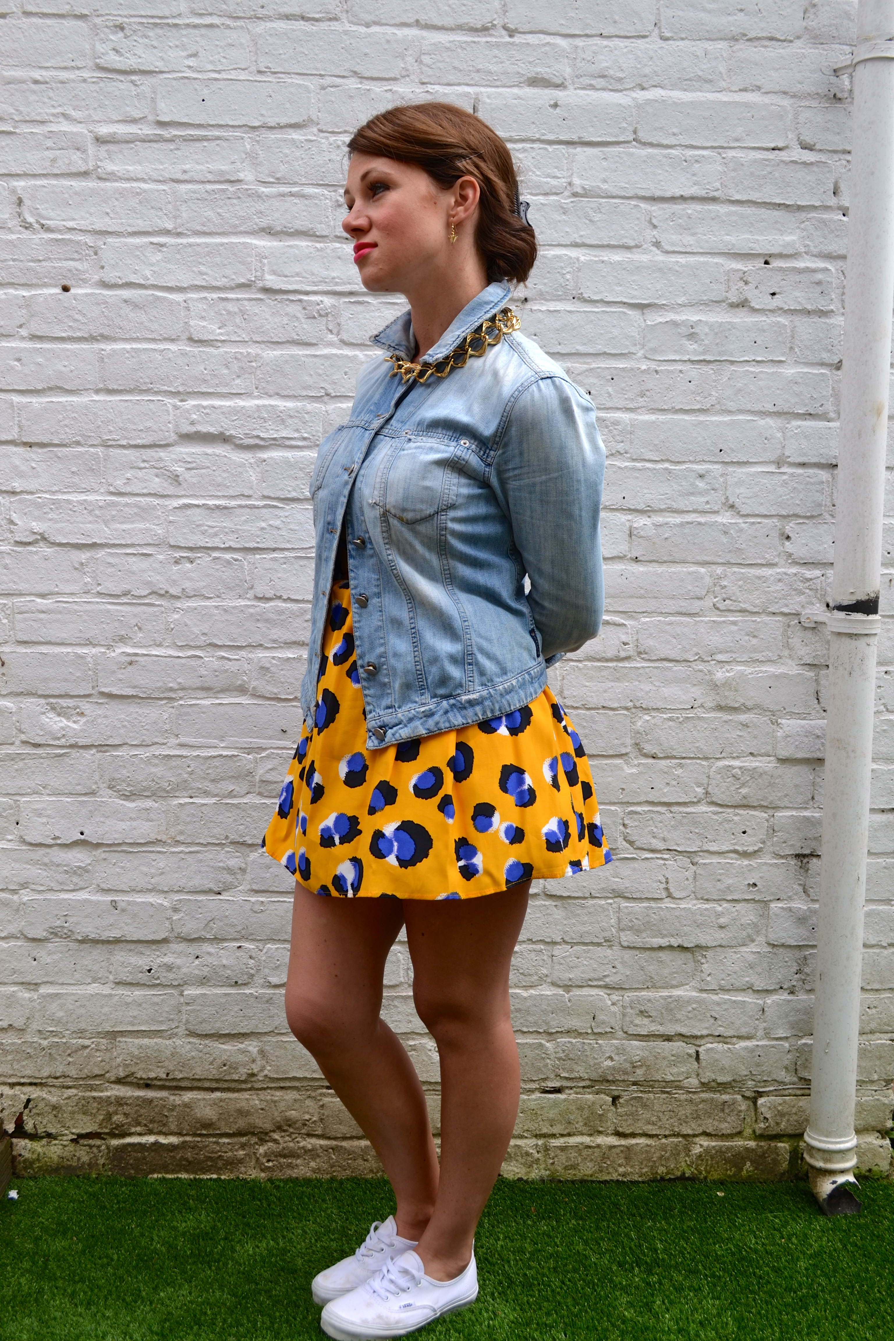 bold printed dress, a denim jacket and white sneakers