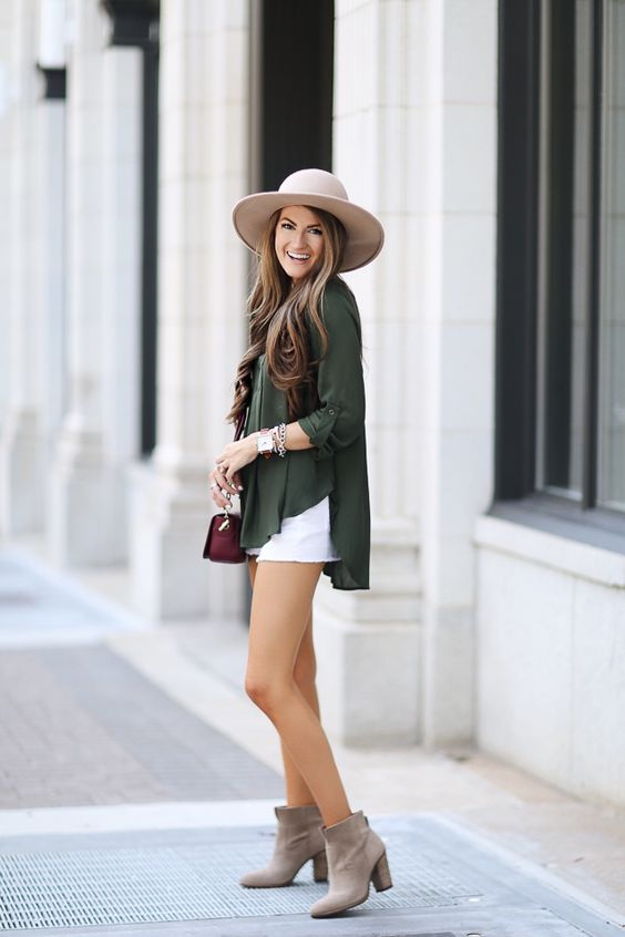 white shorts, a dark green oversized shirt and grey booties