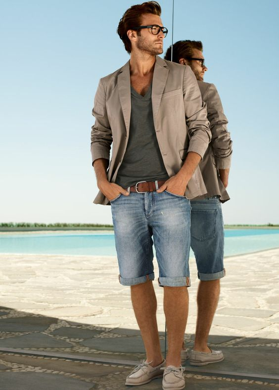 bermuda denim shorts, an olive green tee, a brown jacket and sneakers