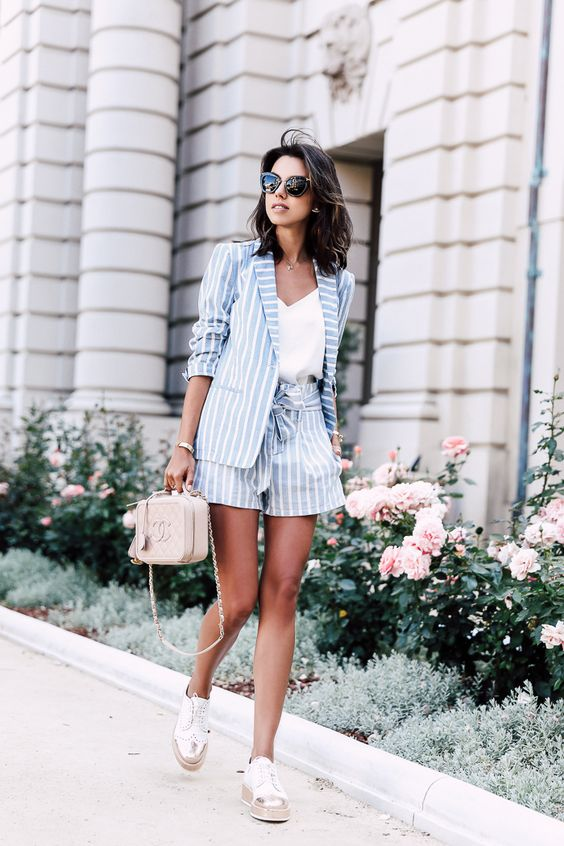 striped shorts, a striped jacket and white sneakers
