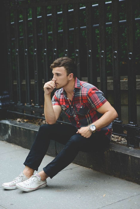 navy jeans, a checked short-sleeve shirt and white Converse