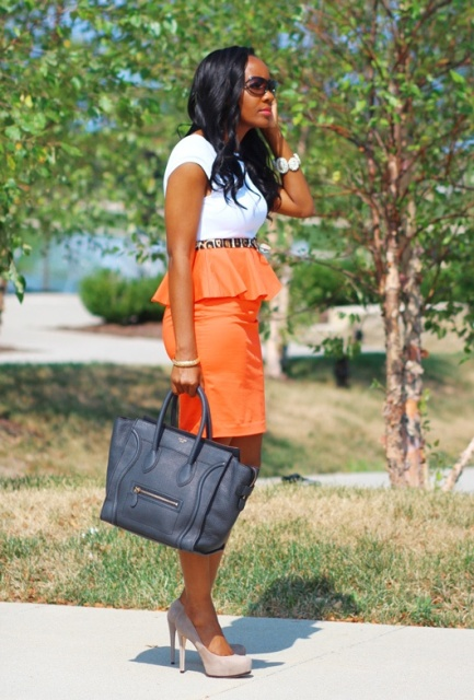 Orange skirt with white t-shirt, printed belt and neutral shoes