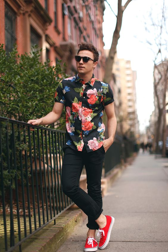 black jeans, a floral shirt and red sneakers