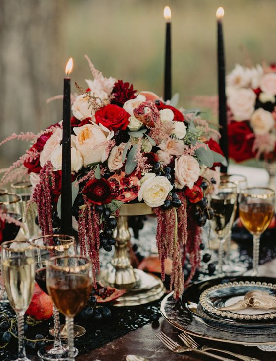 decadent tablescape with a burgundy centerpiece with pomegranates and dripping amaranthus
