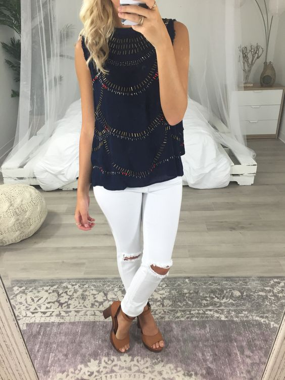 white distressed jeans, a navy patterned top and tan shoes