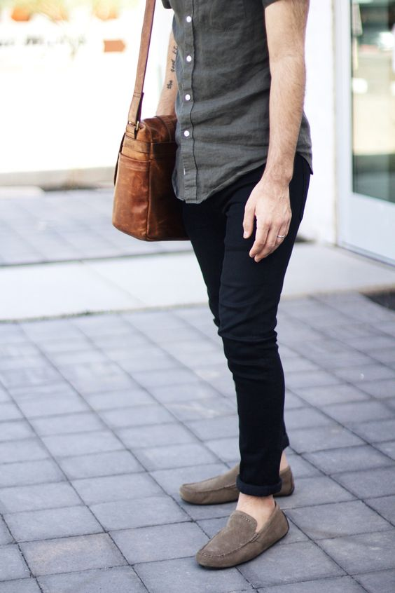 02 black jeans, a grey shirt, grey loafers and a tan bag
