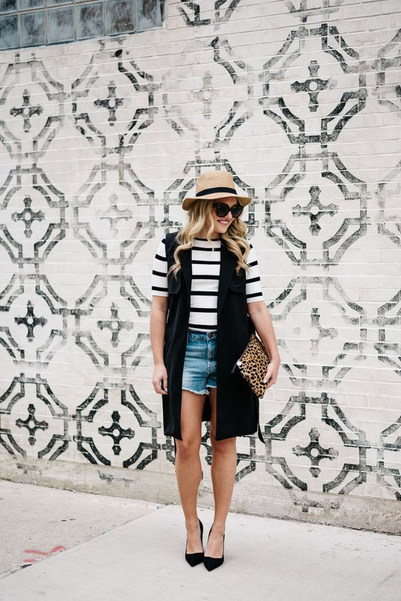 a striped tee, denim cutoff shorts, a long black vest, black Pumps, a leopard clutch