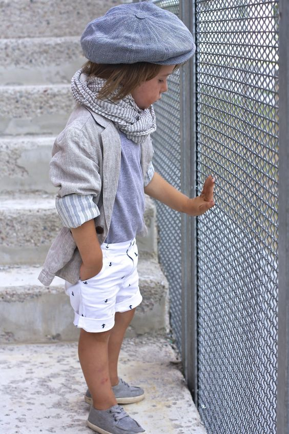 printed shorts, a grey t shirt and jacket and grey sneakers