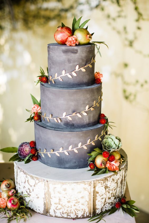 dark grey wedding cake decorated with pomegranates