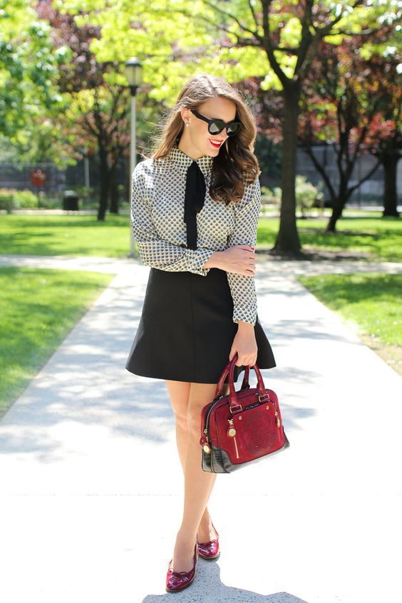 a black trapeze skirt, a printed shirt, a black tie and red shoes