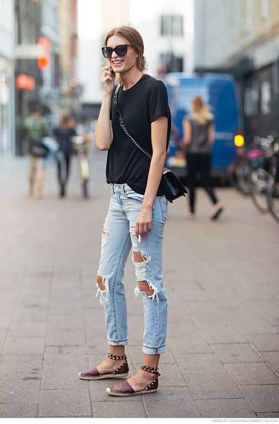 distressed jeans, a blue tee, stud flats and a cross-body bag