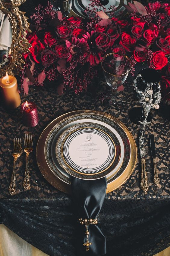 dark black and gold table setting with red roses decor