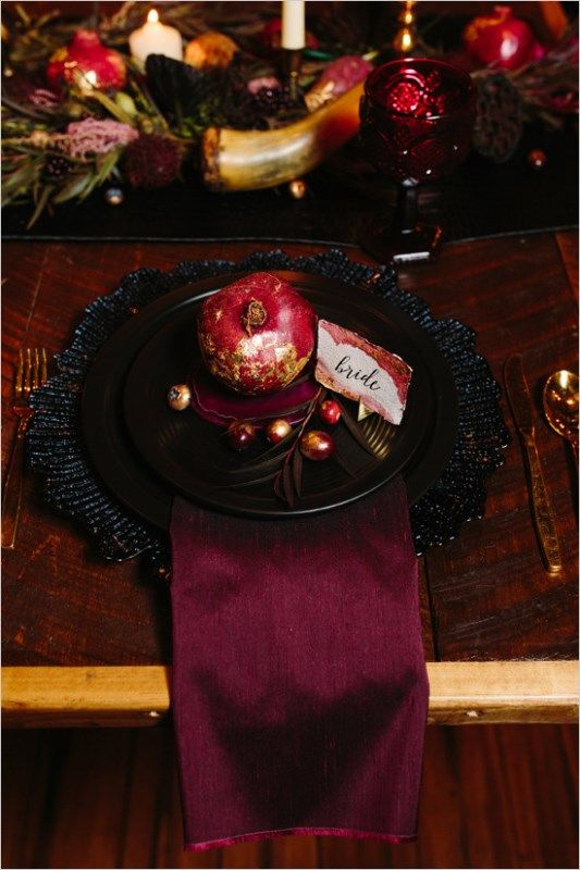 moody dark red and purple wedding table with black dishes and gold tableware