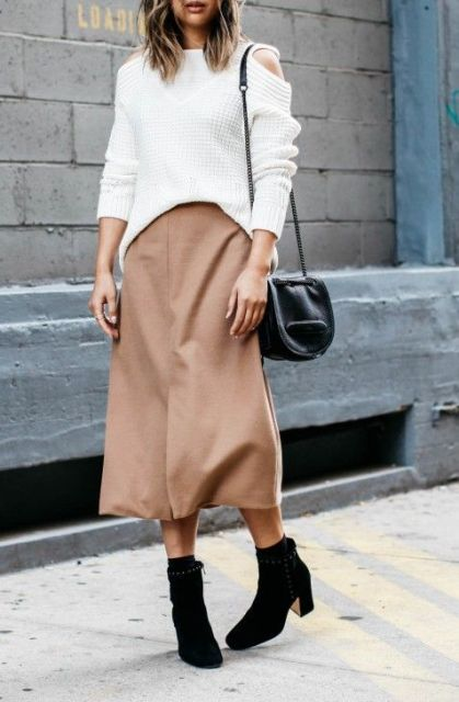 With white loose sweatshirt, mini bag and boots