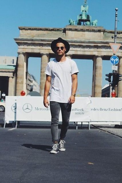 grey jeans, a loose white tee and black shoes