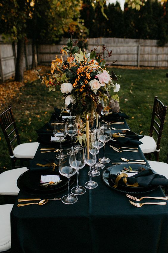 dark fall tablescape with oversized florals, black linens, gold silverware