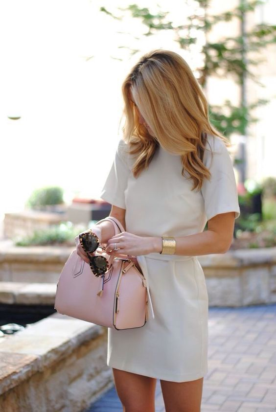 an off-white mini dress with a pink purse and gold accessories