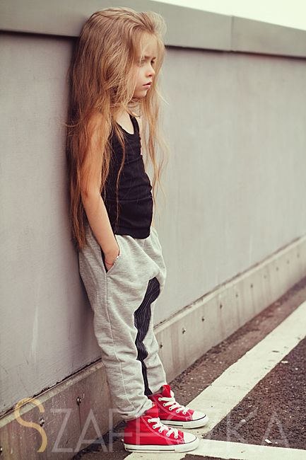 grey sport pants, a black top and red chucks