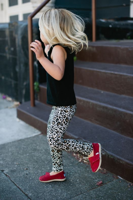 leopard printed pants, a black top and red Vans shoes