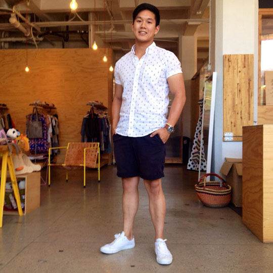 white sneakers, navy shorts and a printed shirt