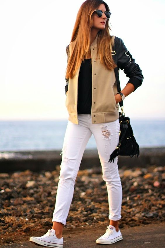 white ripped jeans, a black tee, a black and tan jacket
