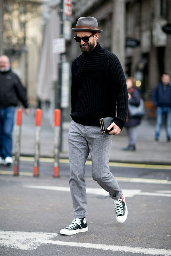 grey trousers, a chunky knit black sweater, black Converse