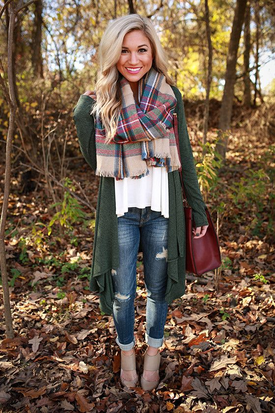 an oversized green cardigan, a white top and a plaid blanket scarf