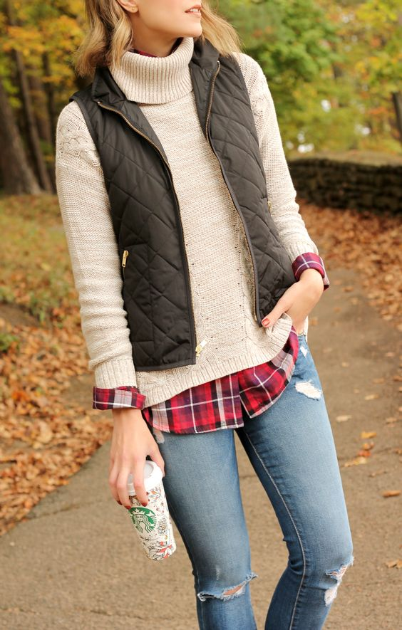 jeans, a plaid shirt, a beige sweater and a grey vest