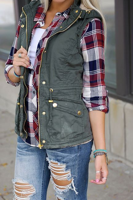 ripped jeans, a white top, a plaid shirt and an olive green vest