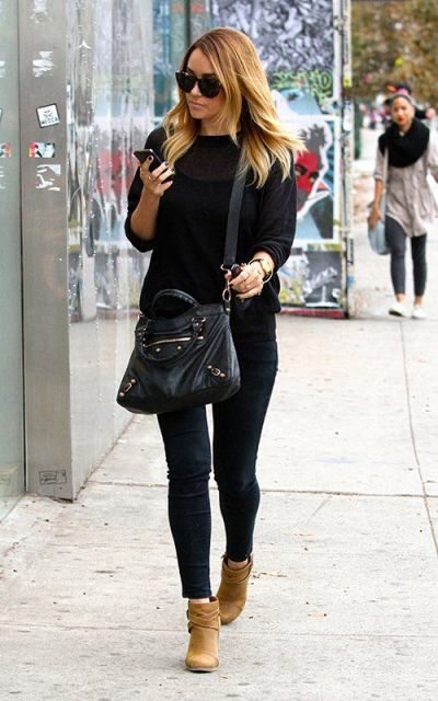 With black shirt, jeans and crossbody bag